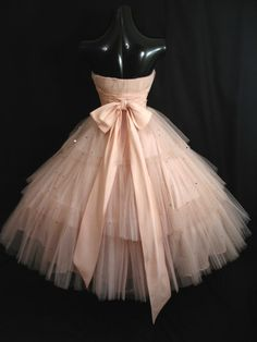 "An absolutely stunning strapless 1950's party/prom dress in an enchanting confection of shell pink layered tulle and taffeta. The soft shade of pink is ethereal and very romantic. This dress was likely originally designed as a wedding or prom gown and is certainly lovely enough to be worn at a very special occasion. Maker's label reads ""Cotillon Formals"", which produced high end bridal and formal wear during the 1950's & 60's."