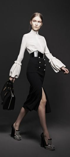 Alexander McQueen Fall 2013; buttoned high skirt; slit; white long sleeve; puffed; white; black; belt;
