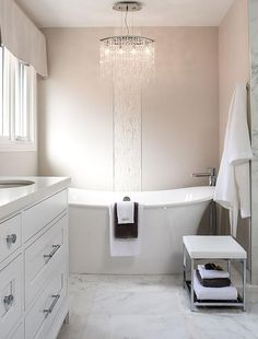 Amazing bathroom features an oval crystal droplets chandelier placed above a freestanding tub and a floor mount tub filler lining a wall accented with a vertical stripe of mosaic tiles.