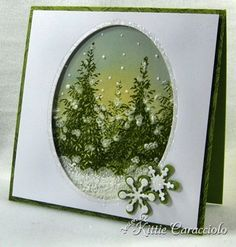 KC Forest of Trees 3 -I stamped the evergreen tree from Flourishes Forest of Trees several times on glossy paper using Olive craft ink and embossed. I sponged on yellow Distress Scattered Straw for the sunset and Bordering Blue for the night sky. I added snow to the ground, trees and falling snowflakes with Liquid Appliqué. I added glitter to the little snowflakes and the bordering edge of the frame.