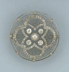 An openwork circular Belle Epoque brooch set with a pearl and circular-cut diamonds, circa 1915