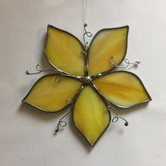 This beautiful stained glass yellow flower suncatcher is made from hand cut glass. The pieces are individually wrapped in lead came and soldered. It comes ready to hang with a sturdy hook and clear line. It measures approximately 5.5 inches in diameter (each flower varies slighlty as they are all hand made). I used copper tinned wire to add fun vines to this piece. The solder is waxed and buffed to shine. This suncatcher will look great in any window or hanging on a wall as a decoration…