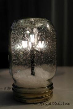 Made with a mason jar, miniature street light found at a dollar store (that really lights up!), glue, white glitter, and fake snow. Reminds me of Mr. Tumnus...