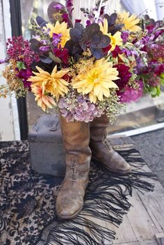 Some beautiful old English riding boots filled with flowers.
