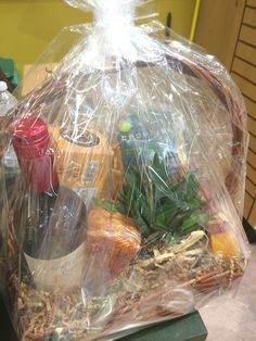 Gift basket with wine, cheese, a marble cheese tray crackers and beautiful succulent plant.