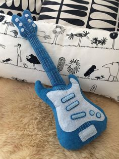 The Plush Cushion-Electric Guitar ROCK is a perfect gift for big and mini rockers!  It hides many embroidery details and finishes hands ... But no buttons that could come off. It is therefore suitable for young children. This is the perfect teddy-pad for a colorful and offbeat decoration!  The Plush Cushion is made of 100% Wool Felt and polyester fiber.  Size (cm): H 53 x L 19  The Plush Cushion-Electric Guitar ROCK is designed and manufactured by hand with care and full of love. It is not…