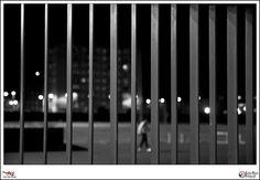 La soledad del atleta - p365jvr - 29 de enero de 2013. 29/365  A veces cuando disparamos el gatillo queremos que el motivo principal de la foto esté resaltado sobre el resto de la imagen. En este caso he evitado hacer esto y mostrar la soledad de una persona entrenándose en una pista vacía, solamente él, el tartán y las luces. Por este motivo de soledad, la rejas de alguna manera aprisionan al atleta y lo retienen.   Espero que os guste.