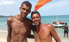 Stromae (Left) standing shirtless flashing his body on a beach...