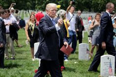 U.S. President Donald Trump (C) holds up a yellow rose while walking through Section 60 at Arlington National Cemetery on Memorial Day May 29, 2017 in Arlington, Virginia. Trump visited with families and layed flowers at the grave of Marine Corps Second Lt. Robert Kelly, the son of Homeland Security Secretary John Kelly.