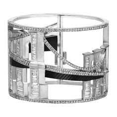 Bridges of New York Bangle Cuff Bracelet in 18K White Gold & Titanium with 671 Diamonds (28 1/2 Cttw) from Jewelrycom  An expression of ultimate luxury this amazing hand-crafted item is the only one of its kind: only one person will ever get to wear this amazing diamond cuff. The 28.5 ct diamond cuff set in 18K white gold with titanium accents captures both the soul and spirit of New York - the iconic 'bones' of Manhattan are incorporated in the design to convey the spirit and tone that are…