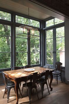 Dining table in room filled with windows. Photo by Lana Kenney (via Apartment Therapy).