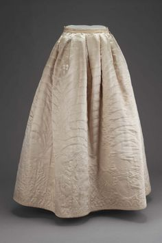 Petticoat; white satin lined with white glazed wool and stuffed with wool fleece; large-scale design of roses with pointed oval leaves quilted in running stitch