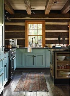 Rustic cabin kitchen with dusty blue shaker cabinets and dark hardwood floors.