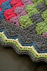 1 rnd of SC in gray as foundation.  1 rnd of one DC in each SC, with 3 in each crnr,   -1 rnd of half shells as from the afghan, with extra DC in the shells on the corners, using gray yarn.  -1 rnd of sc through back of stitch in teal  -1 rnd of sc chevron in pale green, also through back of stitch only.  -1 rnd of sc chevron in medium green, also through back of stitch only.  -1 rnd of sc in gray through back of stitch only, but with an extra sc in each peak stitch to emphasize the points.