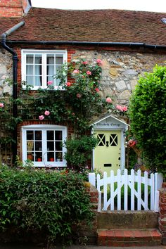 This tiny cottage with roses around the door is situated in a narrow street in the historic village of Bosham in West Sussex. At the rear, the garden goes down to the waters of Chichester Harbour. When tides are very high the street floods hence the concrete barrier in front of the gate.  This cottage, together with the one adjoining it {Bosham Abbey}, date from the 18th century and are Grade II listed properties meaning they are legally protected from development or major alterations.