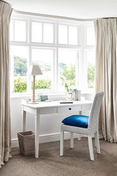 Bedroom work space boasts a bay window dressed in natural linen French pleat drapery panels filled with a white french desk and a white wicker chair adorned with a jewel blue velvet chair.