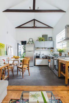 Cozinha integrada de apê compacto tem piso de cimento queimado e móveis soltos como o carrinho de madeira.