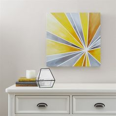 Bring a ray of sunshine with this fun and vibrant abstract piece. The geometric shapes are filled with different shades of grey and yellow that will brighten up your bedroom wall. The 20x20 art piece is printed on canvas and lightly coated with gel for texture.