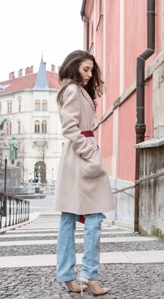 Fashion Blogger Veronika Lipar of Brunette from Wall Street wearing distressed blue Levi's jeans, off-white double breasted Weekend Maxmara coat, red dangling belt, blush Gianvito Rossi plexi pumps, See by Chloe pink top handle bag, blue leather gloves standing on the street of Ljubljana