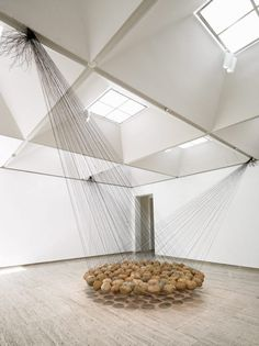 """Up close image of Ken Unsworth's """"Suspended Circle 2"""" installation, featuring river stones suspended above the ground by black wire."""