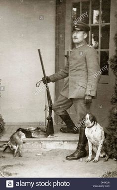 Hunter, a Prussian officer wearing his uniform holding a gun with a hunting dog, a shot hare and a shot pheasant lying next to.