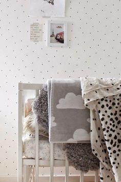 All-white gender neutral nursery with black polka dot walls
