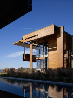 The Malibu Beach House (California) consists of two separate buildings: guesthouse and main house, the grasses and sand are allowed into an entry courtyard as an extension of the beach landscape. The beach houses are clad in teak wood, which also repeats inside as ceiling and floor finishes.