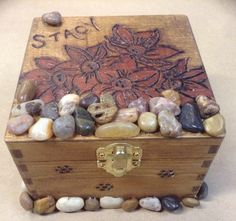 Made by customer request. A wood box wood burned then stained . Small local river rocks adorn the cover & along the bottom.