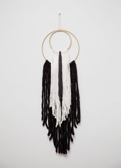 2 gold ring fiber wall hanging. Black and white yarn. 7 wide ring