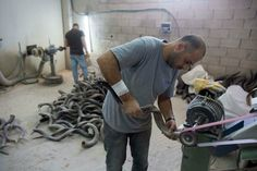 A worker puts the finishing touches on a shofar at a factory in Jerusalem. (Yonatan Sindel/Flash90)