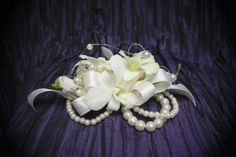 White dendrobium orchids on a white ribbon with gold accents on an ivory pearl corsage bracelet. #prom #corsage