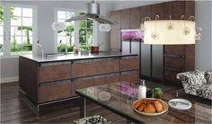 In deze opstelling van de INO keuken worden oud en nieuw fantastisch gecombineerd. Roestig gekleurde fronten, houten vloer en eettafel enerzijds en designer afzuigkap, strakke kranen en bijzondere verlichting anderzijds. Het kookeiland is ontzettend breed, er kan gemakkelijk aan beide kanten gewerkt worden. Je creeërt hiermee een boel extra opbergruimte.