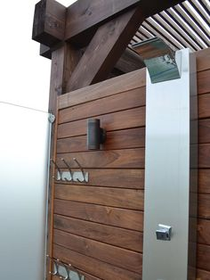 A contemporary stainless steel fixture and frosted glass enclosure refine this outdoor shower.