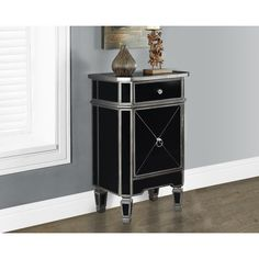 This black mirror finish paired with contrasting metallic charcoal trim will add bold sophistication to any décor. Featuring one storage drawer and a closed cabinet, this piece will help keep you organized in style.