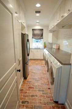 Galley style combo laundry space & pantry with Chicago brick floors, front load washers & dryers, glossy white subway tiles backsplash, stainless steel fridge, white & gray roman shade and white utility cabinets with gray countertops