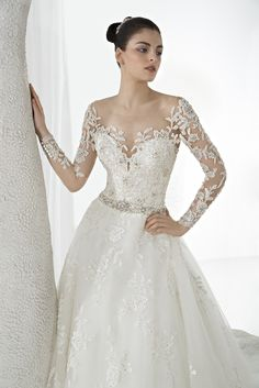 Illusion scoop neck with sheer embellished long sleeves and beaded waist. #DemetriosBride Style 648.