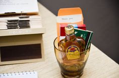 "Mad Men party favors: Mini whiskey bottle, candy cigarettes, vintage matchbook, and ""thank you"" note in a mini manila envelope... all inside a whiskey glass!  www.everybodysinvited.in"