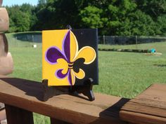 LSU and New Orleans Saints Fleur de lis painted on tile. Sport this for your team.