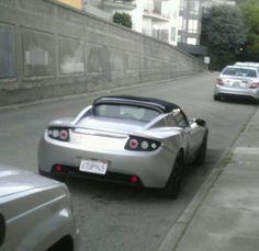 100k Tesla parked on street.