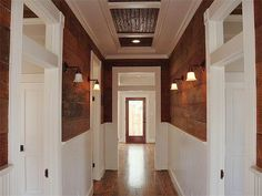 The hallway has exposed shiplap on the walls and transoms over the doors, which add such architectural detail .