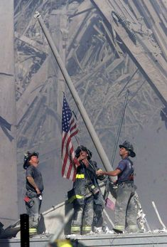 Firefighters raise a U.S. flag at the site of the World Trade Center after two…