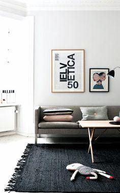 Black rug + gray sofa + white wall Via Coco Lapine