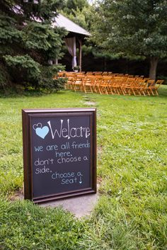a pretty famed chalk board telling guests to sit wherever they like as they come into the ceremony - thereddirtbride.com - see more of this wedding here