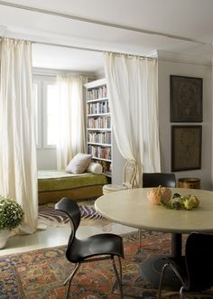 Tucked behind white, airy curtains a relaxing day bed makes an ideal spot to curl up for a nap.