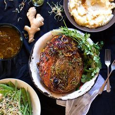A recipe for slow roasted leg of pork with an Asian basting sauce, served with an easy ginger and coriander pesto and all the trimmings.