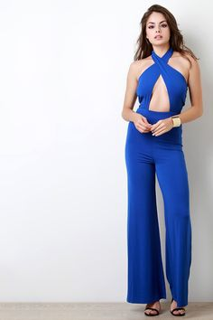 This daring jumpsuit features a smooth stretchy knit fabric, crisscross band chest design, open back construction, and halter neckline. Finished with a wide leg, relaxed fit bottoms, and button hook closure at nape.
