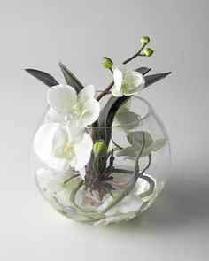 """Add exotic beauty and color to home decor with this unique arrangement featuring creamy white phalaeopsis orchids and foliage immersed in acrylic """"water"""" inside a clear glass bowl."""