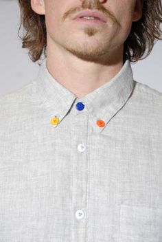 add a touch of whimsy to your shirt by strategically switching out plain buttons with colored ones