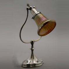 """Tiffany Studios Silvered Bronze Desk Lamp with Shade. The articulated lantern form standard raised on a weighted hat form base, the bronze with a silver finish, the inverted bell form favrile glass shade with violet and green highlights, the lamp base stamped """"Tiffany Studios New York"""" """"418"""", the shade signed """"L.C.T."""". 1899-1918"""