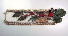 Holly, berries and a gold ribbon wrap up this bead loomed Christmas Cuff. The clasp is also adorned with hand woven holly and beaded bead berries.